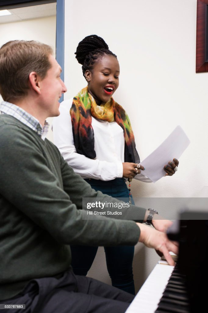 Vocal teacher and student singing at piano : Foto stock