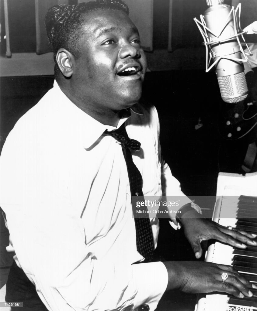 R&B vocalist Fats Domino plays piano while singing into a vintage microphone in circa 1958.