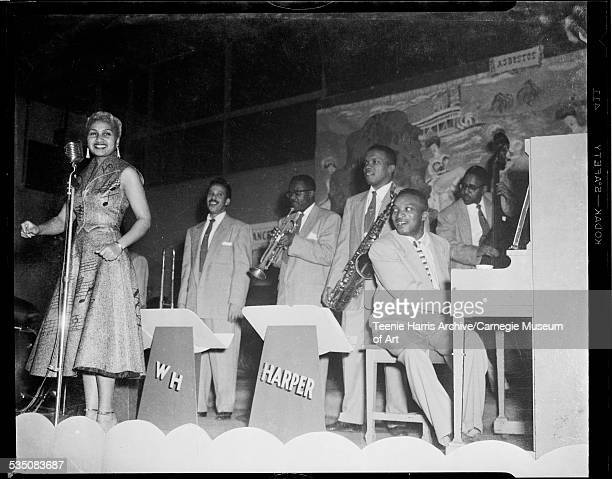 Vocalist Tiny Irvin wearing dress with musical notes performing with Walt Harper band including drummer Harold 'Brushes' Lee Jon Morris on trombone...