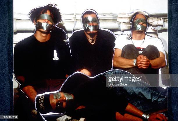 Vocalist Zack de la Rocha bassist Tim Comerford and drummer Brad Wilk are seated on the floor behind recumbent guitarist Tom Morello all bound gagged...
