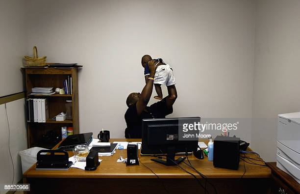 Vocational counselor John Allison lifts a homeless baby, age six months, at the Family Gateway family homeless shelter on June 15, 2009 in Dallas,...
