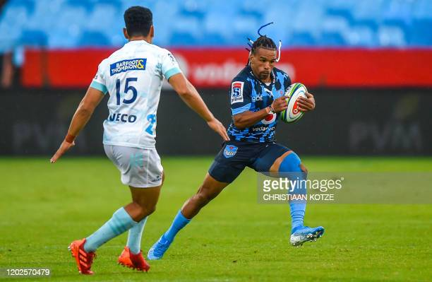 Vodacom Bulls' South African wing Rosko Specman runs with the ball past The Blues' New Zealand flyhalf Stephen Perofeta during the Super Rugby match...