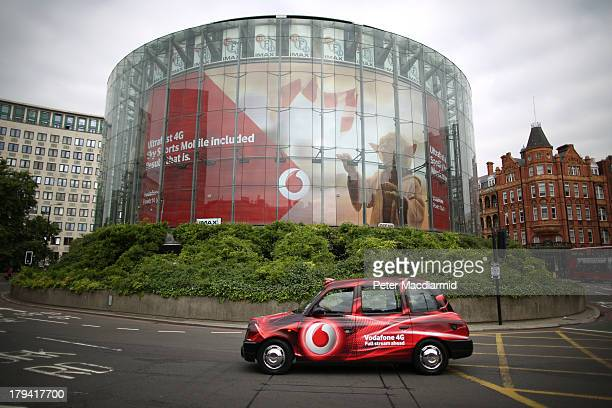 Vodafone branded taxi passes a logo on a billboard at the Imax cinema September 3, 2013 in London, England. Vodafone has agreed to sell it's 45...