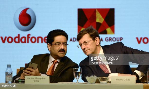 Vodafone Group CEO Vittorio Colao listens to chairman of India's Aditya Birla Group Kumar Mangalam Birla during a news conference in Mumbai on March...