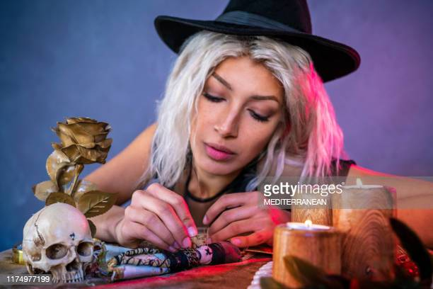 vodoo girl with nails on table and witch hat - ceremony stock pictures, royalty-free photos & images