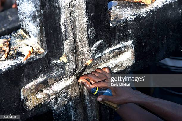 Vodou believers visit a cross dedicated to Baron Samedi the head of the Gede family of spirits the spirits of the dead in the National Cemetery in...