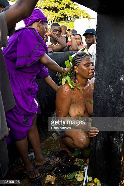 Vodou priestess or mambo baths a woman to facilitate her passage into the spirit world in front of a cross dedicated to Baron Samedi the head of the...