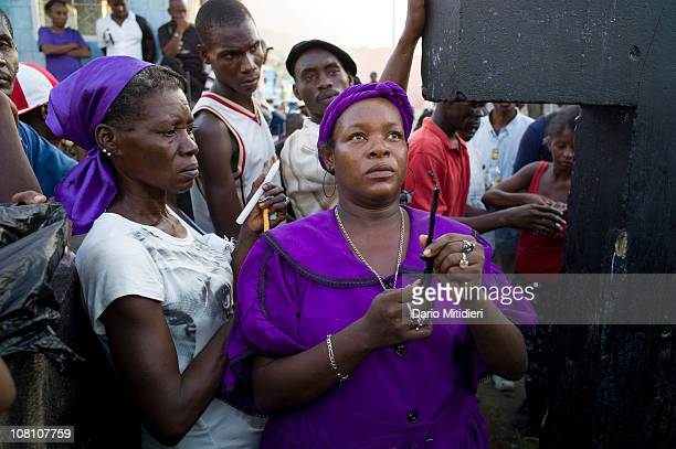 Vodou priestess or mambo offers a candle to the cross dedicated to Baron Samedi the head of the Gede family of spirits the spirits of the dead in the...