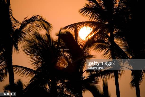 a vog (volcano fog) shrouded sunset, kamekahonu beach, kailua kona. - kailua beach stock photos and pictures