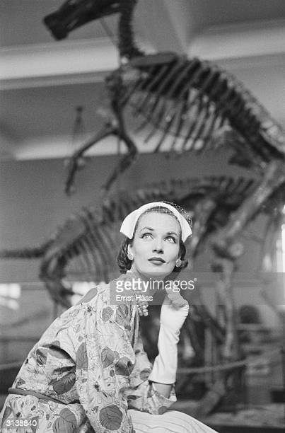 Vogue fashion model posing in front of a dinosaur skeleton in a New York museum