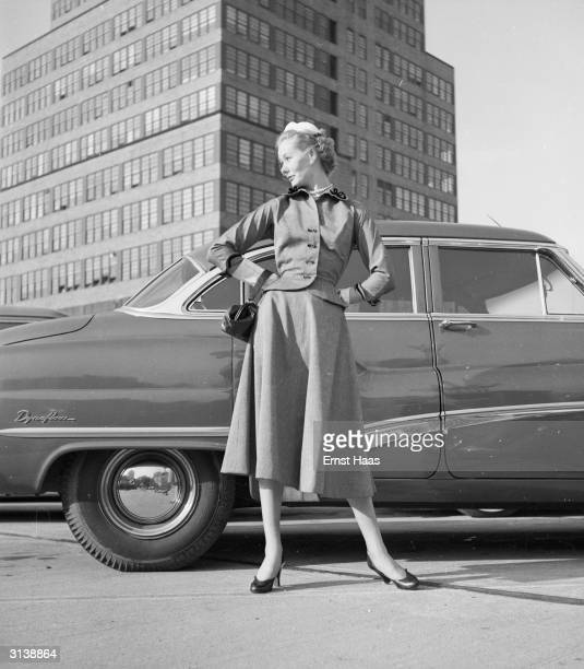 Vogue fashion model standing in front of a car in the shadow of the McGraw Hill building on West 42nd Street New York