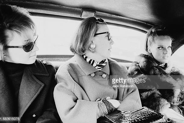 Vogue magazine style editor Carrie Donovan rides in a car with the model Veruschka , 1966. The figure on the left is unidentified.