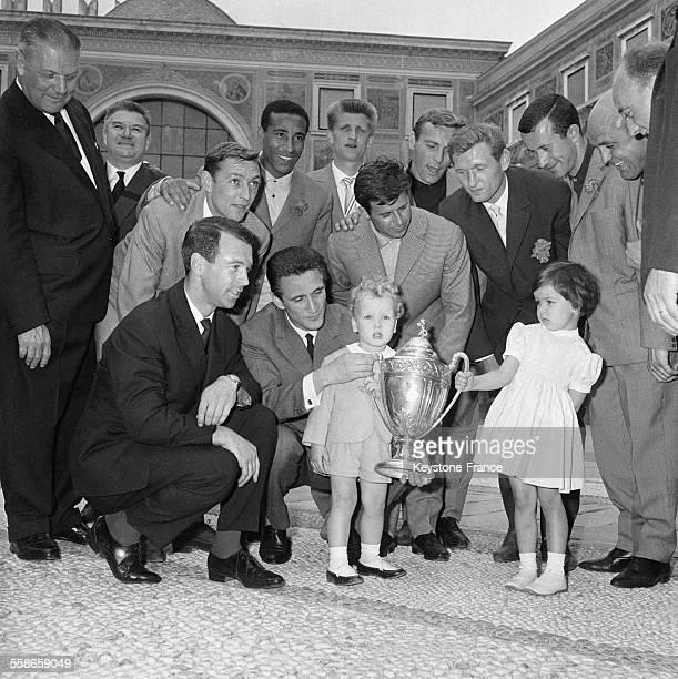 Voici les joueurs de l'AS Monaco entourant la coupe que tiennent le prince Albert et la princesse Caroline de Monaco à gauche près du prince Raymond...