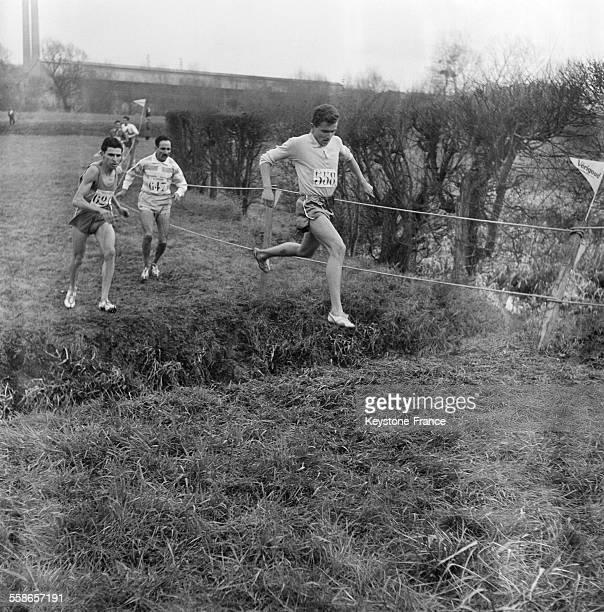 Voici un passage de la rivière en tête le vainqueur Michel Jazy suivi de Chiclet et Mimoun à MaisonsLaffitte France le 14 février 1960