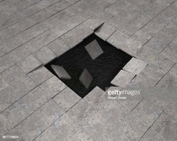 void opening up beneath paving stones - sinkhole stock photos and pictures