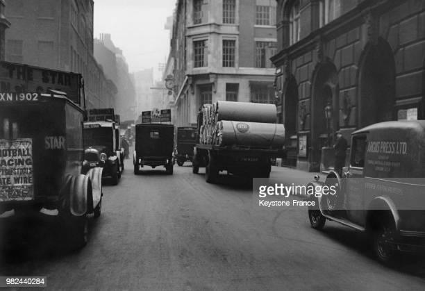 Voitures publicitaires transportant les journaux et camion transportant des rouleaux de papier dans Fleet Street à Londres en Angleterre au...