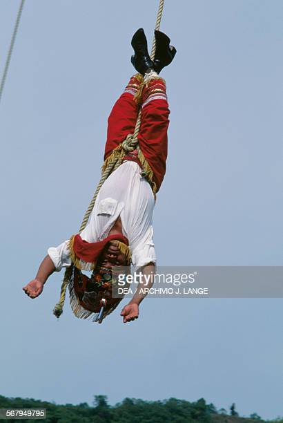 Volador hanging in the air after launching from the platform atop the pole El Tajin Veracruz Mexico