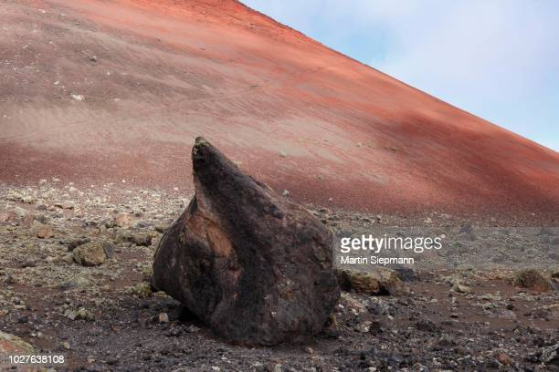 volcanic bomb in front of montana colorada volcano, lanzarote, canary islands, spain - paisaje volcánico fotografías e imágenes de stock