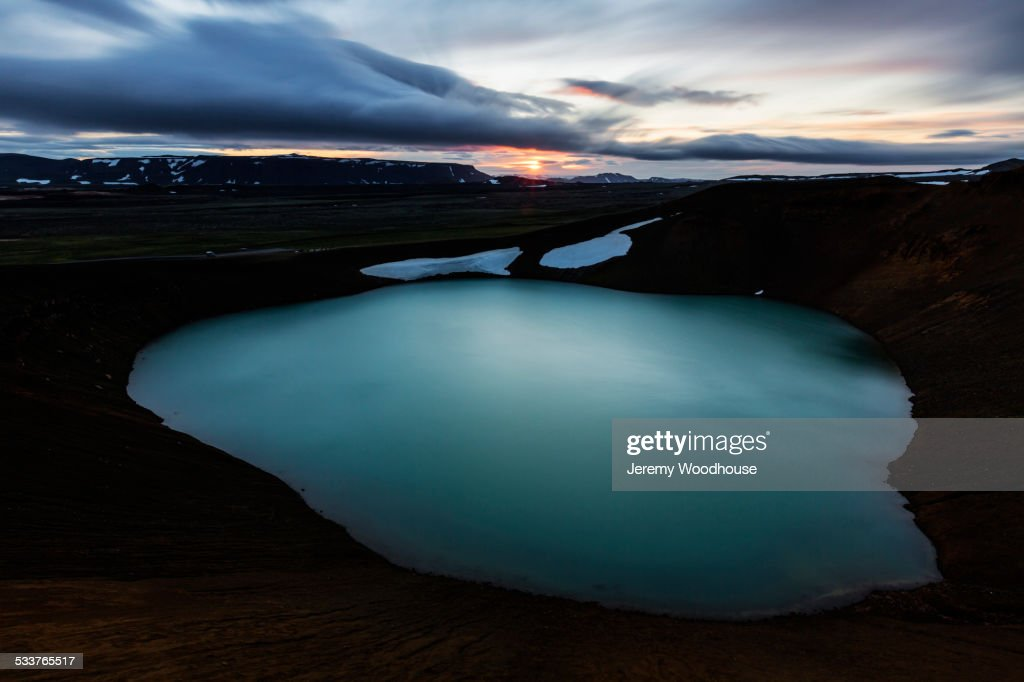 Volcanic crate pool in rock formations under sunset sky : Foto stock