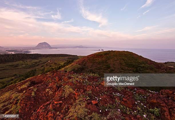 volcanic crater and hills at sunset - jeju stock-fotos und bilder