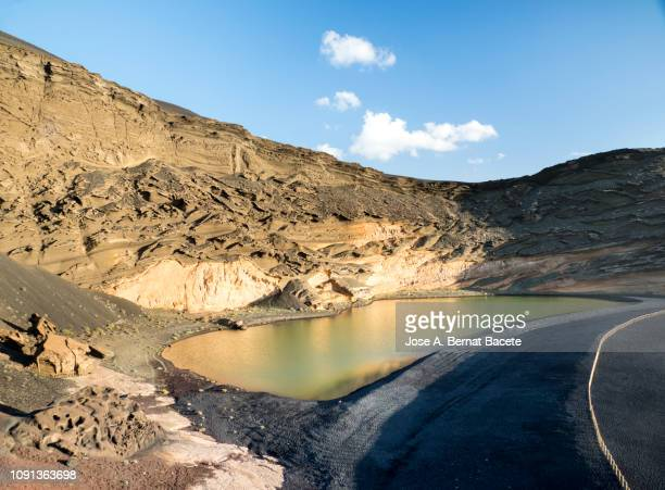 volcanic landscape with mountains and craters and a lake in the volcanoes natural park , lanzarote, canary islands, spain. - área silvestre fotografías e imágenes de stock