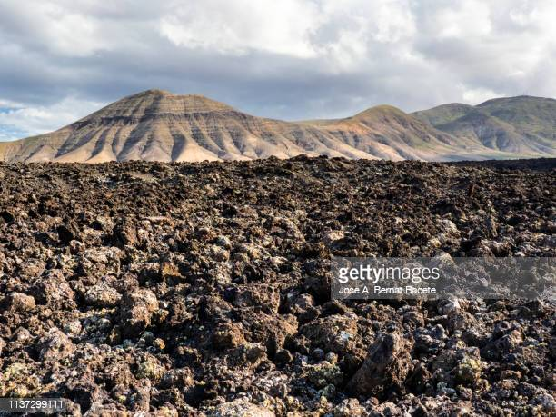 volcanic landscape with mountains and craters one day of blue sky with white clouds. lanzarote island, canary islands, spain. - atlantic islands stock pictures, royalty-free photos & images