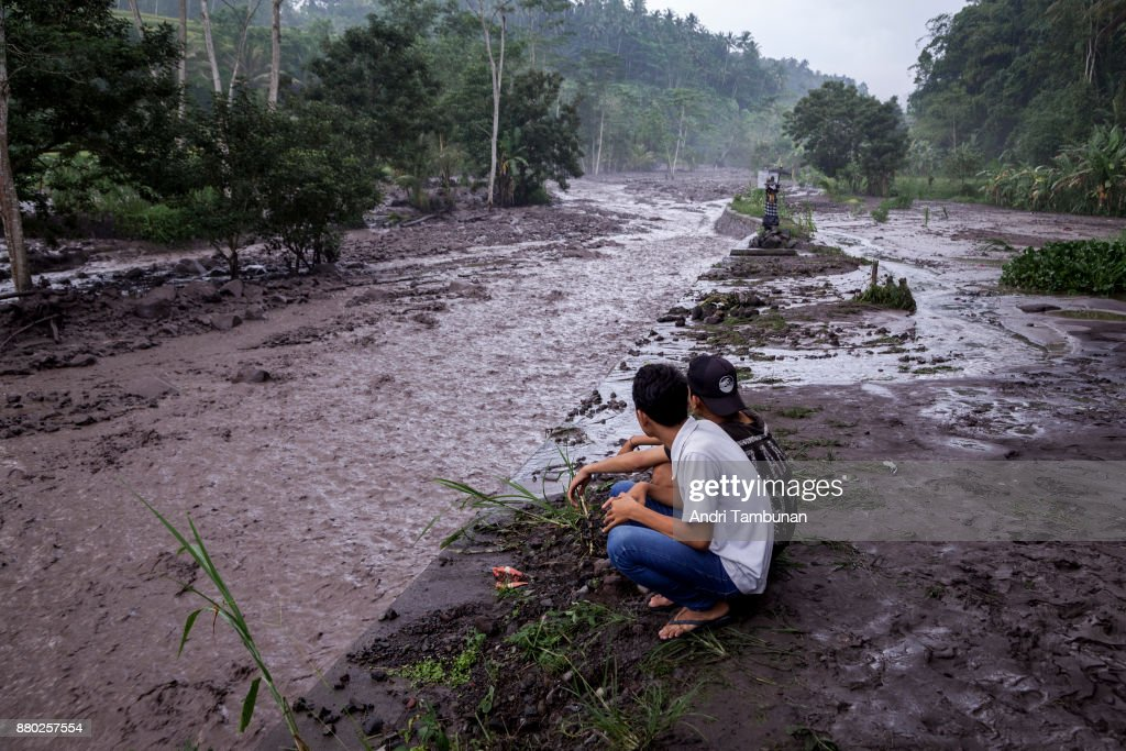 KARANGASEM, BALI, INDONESIA - NOVEMBER 27: Volcanic material from Mount Agung flows through a local river in Gesing Village while villagers are seen watching nearby on November 27, 2017 in Karangasem, Island of Bali, Indonesia. Indonesian authorities raised the state of alert to its highest level for the volcano, Mount Agung, after thick ash started shooting thousands of meters into the air with increasing intensity. Based on reports, as many as 100,000 villagers will need to leave the expanded danger zone while tens of thousands of tourists have been stranded due to airport closures.