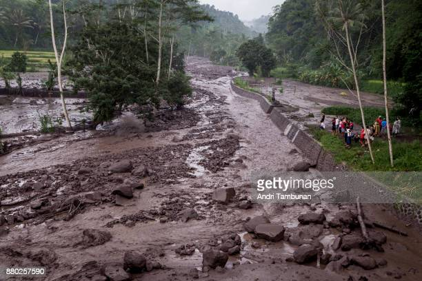 KARANGASEM BALI INDONESIA NOVEMBER 27 Volcanic material from Mount Agung flows through a local river in Gesing Village while villagers are seen...