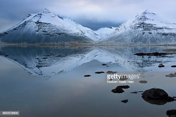 volcanic mountains in winter with reflection in the water, near djupivogur, east island, island - austurland stock pictures, royalty-free photos & images