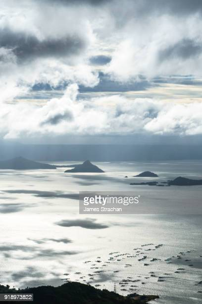 volcanic peaks in early morning light spread across lake taal, itself the result of eruptions over 100,000 years ago, tagaytay, luzon island, philippines - taal volcano stock photos and pictures