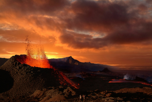 Volcano erupting at night spewing orange lava 94988839