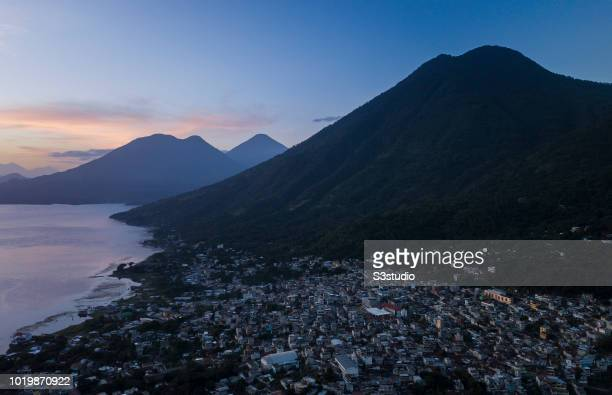 Volcano San Pedro and San Pedro la Laguna are seen under the light of sunrise at the shores of Lake Atitlan on 12 August 2018 in the Solola...