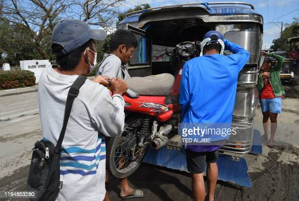 Volcanoaffected residents returning to their homes for the day load a motorcycle onto a jeepney to be brought back to an evacuation centre in Tanauan...
