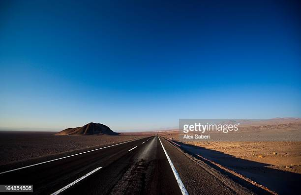 volcanoes and a road in the atacama desert at sunset. - alex saberi stockfoto's en -beelden