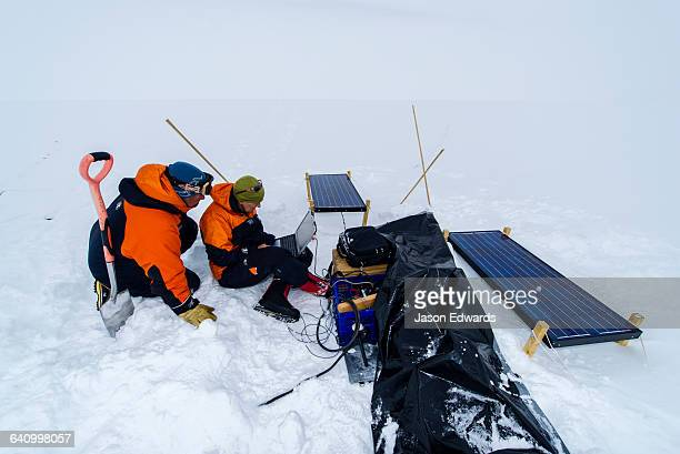 Volcanologists on a frozen plain monitor a volcano research sensor with a laptop computer.