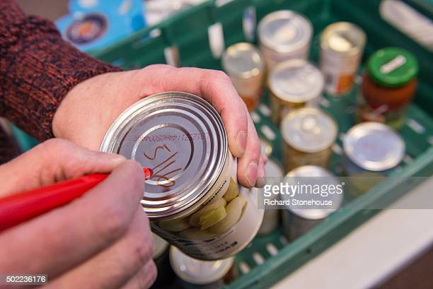 Volenteers collate donated food writing on clear use by dates and placing them in trays with similar food types at the Trussell Trust Food Bank on...