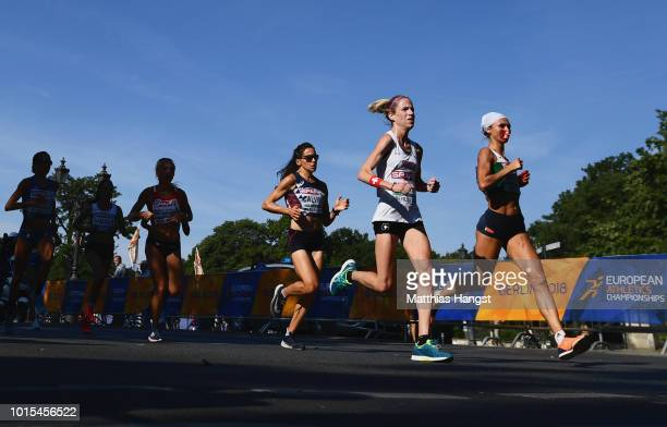 Volha Mazuronak of Belarus runs with a nosebleed alongside Martina Strahl of Switzerland in the Women's Marathon final during day six of the 24th...
