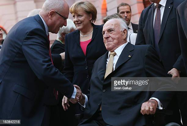 Volker Kauder head of the Bundestag faction of the German Christian Democrats greets former German Chancellor Helmut Kohl as German Chancellor Angela...