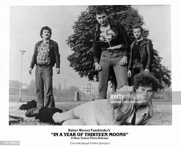 Volker Spengler laying on the ground with his pants down around his ankles exposing the women stockings he has on as three men stand staring above...