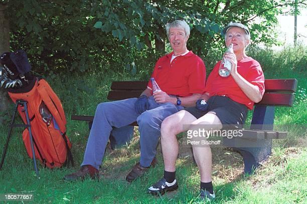 Volkert Kraeft Ehefrau Edeltraut Golfplatz Bank Mineralwasser trinken Golf Golfset Golftasche Kappe sitzen Schläger ausruhen Frau Mann Ehemann...