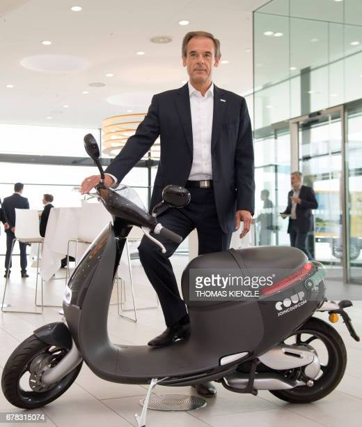 Volkmar Denner CEO of German technology concern Bosch stands next to an electric scooter during the company's annual press conference at the Bosch...