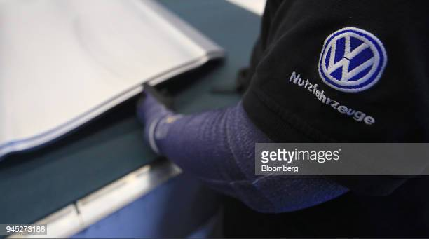 A Volkswagen AG commercial vehicles logo sits on an employee's sleeve employee during automobile door quality checks inside the Volkswagen AG factory...