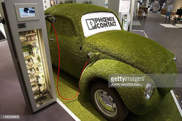 A Volkswagen Beetle covered in grass and charging by an electricity outlet is featured at the stand of German firm Phoenix Contact which manufactures...