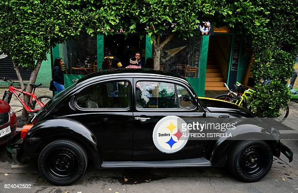 A Volkswagen beetle painted in the colors of US American football team Pitsburgh Steelers remains parked outside the Malafama bar of Condesa...