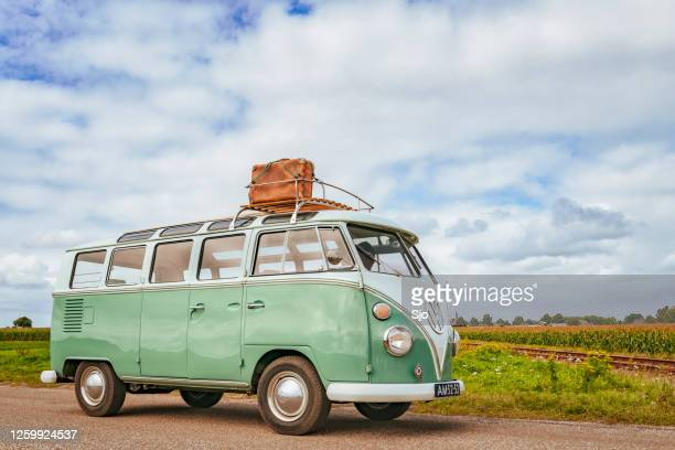 volkswagen bus type 2 t1 camper van driving through the countryside - volkswagen stock pictures, royalty-free photos & images