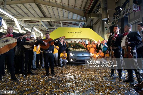 TOPSHOT Volkswagen employees pose with a Beetle the final edition of the iconic car at a factory in Puebla Puebla State Mexico on July 10 2019 The...