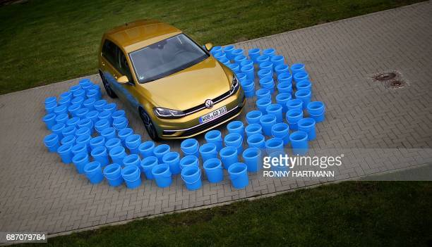 A Volkswagen Golf 7 automobile frames by 114 plastic buckets each filled with ten liters of water pictured in Wolfsburg central Germany on May 19...