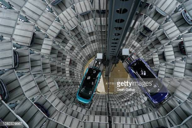 Volkswagen ID.4 and ID.3 electric cars stand on elevator platforms inside one of the twin towers used as storage at the Autostadt promotional...