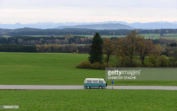 Volkswagen Kombi owner Wanja Fuhrmann poses in front of his Volkswagen T2 camper van built in the year 1975 on a road near Landsberg, southern...