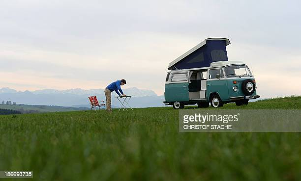 Volkswagen Kombi owner Wanja Fuhrmann sets up a camping table next to his Volkswagen T2 camper van built in the year 1975 near Landsberg, southern...